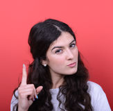 Portrait of woman threatening with finger gesture against red ba Stock Photography