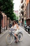 Portrait of a woman tourist in white dress standing with map and bicycle in europe city center of Barcelona.Traveling in stock image