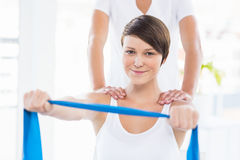 Portrait of woman with trainer holding resistance band Stock Images