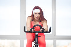 Portrait of woman training on cycling machine in fitness center Royalty Free Stock Photography