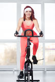 Portrait of woman training on cycling machine in gym Stock Images