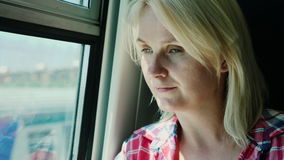 Portrait of a woman traveling on a train. She looks out the window, sunlight glinting on her face stock video