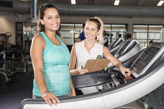 Portrait of woman on treadmill and trainer Stock Photo