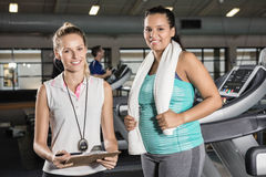 Portrait of woman on treadmill and trainer Stock Photos