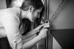 Portrait of woman trying to open lock on fridge Stock Images