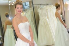 Portrait woman trying on wedding dress in boutique Royalty Free Stock Photo