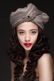 Portrait of a woman in turban. Portrait of a beautiful woman with red lips in turban isolated on dark background Royalty Free Stock Image