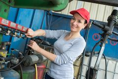 Portrait woman turning on industrial gas supply Stock Image