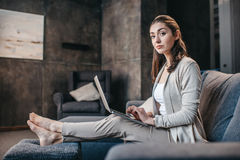 Portrait of woman typing on laptop and relaxing on sofa at home Stock Photos