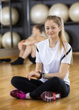 Portrait Of Woman Using Activity Tracker While Sitting In Gym Stock Photography