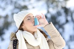 Woman using asthma inhaler in a cold winter. Portrait of a woman using an asthma inhaler in a cold winter with a snowy mountain in the background stock photo