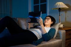 Portrait of woman using digital tablet pad. At night watching interesting video online and lying down on the sofa in the living room at home with holiday Royalty Free Stock Photography