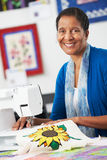 Portrait Of Woman Using Electric Sewing Machine. And Smiling to Camera Stock Photo