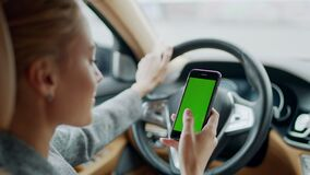 Portrait of woman using greenscreen phone at car. Woman holding smartphone