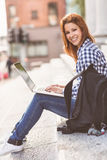 Portrait of a woman using her laptop and smiling at camera Royalty Free Stock Images