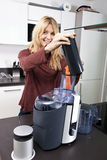 Portrait of woman using juicer for juicing carrots at kitchen counter Royalty Free Stock Photography