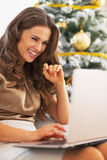 Portrait of woman using laptop in front of christmas tree Stock Image