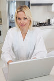 Portrait of a woman using laptop in kitchen. Portrait of a young woman using laptop in the kitchen at home Stock Image