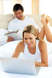 Portrait of woman using a laptop lying on bed Stock Photo