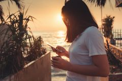 Portrait of Woman is Using Smartphone at The Beach Duration Summer Vacation, Asian Tourist is Relaxing With Her Cell Phone on The. Beach in Holiday Time royalty free stock photos