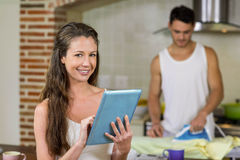 Portrait of woman using tablet in kitchen. Portrait of women using tablet in kitchen while men ironing a shirt in background Stock Image