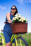 Portrait of woman with vintage bicycle and flowers in wicker bas Stock Image