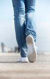Portrait of a woman walking outdoors in comfortable white shoes. Close up portrait of a woman walking outdoors in comfortable white shoes Royalty Free Stock Image