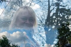 Portrait of a woman walking in park through reflection in glass, which reflects trees and clouds