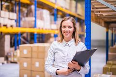 Portrait of a woman warehouse worker or supervisor. Portrait of a young woman warehouse worker or supervisor with clipboard stock photography