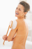 Portrait of  woman washing with body brush in bathtub Stock Images