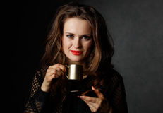 Portrait of woman with wavy brown hair holding cup of coffee Stock Image