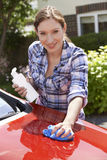 Portrait Of Woman Waxing Car Outside House Royalty Free Stock Image