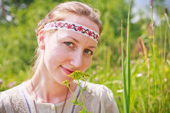 Portrait of a woman wearin Russian national dress. Young woman wearing Russian national dress sitting on a meadow and holding a yellow flowers Royalty Free Stock Photos
