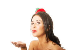 Portrait of a woman wearing elf clothes blowing kiss, looking at the camera Royalty Free Stock Photo