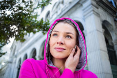 Portrait of a woman wearing a pink jacket putting her headphones Royalty Free Stock Image