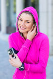 Portrait of a woman wearing a pink jacket putting her headphones Stock Image