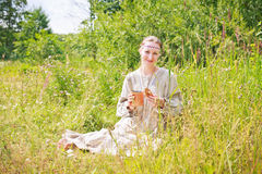 Portrait of a woman wearing Russian national dress. Young woman wearing Russian national dress sitting on a meadow and holding a basket of birch with black Stock Photos