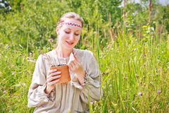 Portrait of a woman wearing Russian national dress. Young woman wearing Russian national dress sitting on a meadow and holding a basket of birch with black Stock Images