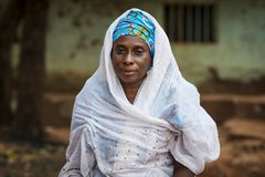 Portrait of a woman wearing a traditional dress with veil, at the Missira neighborhood in the city of Bissau, Guinea Bissau. Bissau, Republic of Guinea-Bissau royalty free stock photo