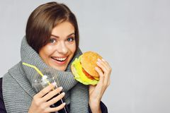 Portrait of woman wearing warm scarf eating fast food. Isolated on gray Stock Photography