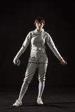 The portrait of woman wearing white fencing costume  on black Royalty Free Stock Photo