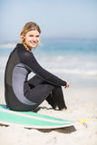 Portrait of woman in wetsuit sitting with surfboard on the beach Stock Images