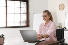 Portrait of woman in wheelchair working with laptop at table stock images