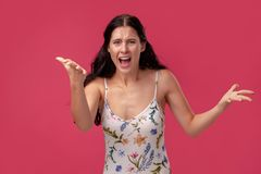 Portrait of a pretty young woman in a light dress standing on pink background in studio. People sincere emotions. Portrait of a woman in a white dress with royalty free stock photos