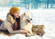 Portrait of woman and white Samoyed dog lying on the snow. In winter day Royalty Free Stock Image