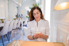 Woman in restaurant using mobile phone Stock Photos