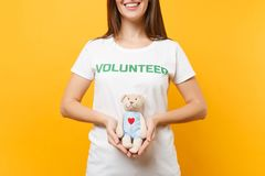 Portrait of woman in white t-shirt with written inscription green title volunteer hold teddy bear plush toy isolated on. Yellow background. Voluntary free royalty free stock photo