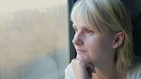 Portrait of a woman who travels by train, looks out the window. The beginning of a new way of concept. 4K video stock footage