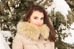 Young woman in winter park. Portrait of woman in winter park near the winter tree Stock Photos