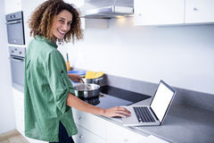 Portrait of woman working on laptop while cooking Royalty Free Stock Photo